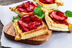 Puff pastry pies with plums, apples, mint and honey Stock Photography
