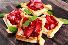Puff pastry pies with plums, apples, mint and honey. Royalty Free Stock Photo