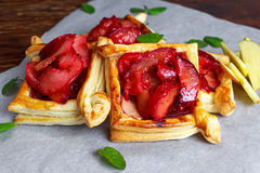 Puff pastry pies with plums, apples, mint and honey Royalty Free Stock Photos