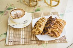 Puff pastry pigtale and cup of cappuccino coffee Royalty Free Stock Image