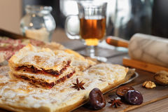 Puff pastry Plum cake. Sprinkled with powdered sugar in the kitchen with tea and walnuts. Flat square pie made of puff pastry with juicy cherry jam and powdered royalty free stock images