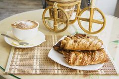 Puff pastry rolls and cup of cappuccino coffee Royalty Free Stock Photography