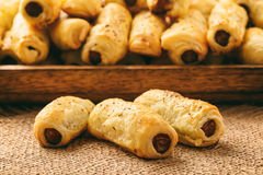 Puff pastry sausage rolls on brown wooden background. Royalty Free Stock Photography