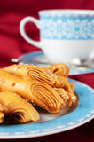 Puff pastry with sesame seeds on a blue cup. Stock Photography