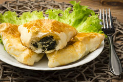 Puff pastry with spinach and feta (triangles) on the wooden background. Royalty Free Stock Photography