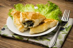 Puff pastry with spinach and feta (triangles) on the wooden background. Royalty Free Stock Photo