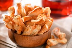 Puff pastry sticks cookies close-up in wooden bowl on table Royalty Free Stock Photos