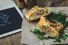 Puff pastry stuffed with meat, carrots, potato pie, decorated with rucola, on a dark background Background for postcard. Menu, res stock images