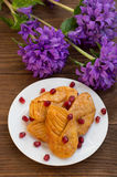 Puff pastry in sugar syrup with the pomegranate. Wooden table. Close-up stock photo