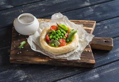Puff pastry tartlet with egg, green peas and tomatoes. Royalty Free Stock Photo