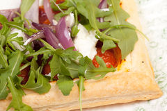 Puff pastry with tomatos onions rocket salad and goats cheese Stock Photo