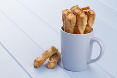 Puff pastry twists. A blue mug with puff pastry twists sprinkled with sugar on a blue wooden table Royalty Free Stock Image