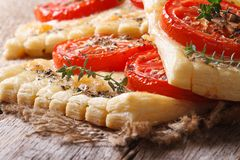 Puff pie with tomato, cheese and herbs macro. Horizontal Stock Image