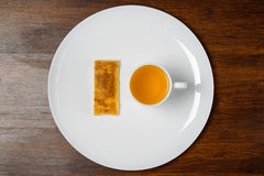Puff and tea on a plate. Puff and a cup of tea on a white plate on background wooden table Royalty Free Stock Images
