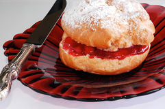 Puffed pastry. With knife, on red glass plate Stock Images
