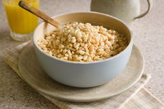 Puffed Rice Cereal. Puffed rice breakfast cereal in a wooden bowl with juice and a milk jug stock photo