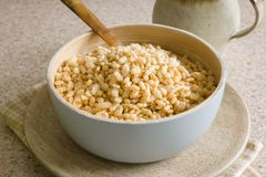 Puffed Rice Cereal. Puffed rice breakfast cereal in a wooden bowl stock photo
