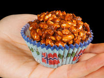 Puffed rice chocolate cake in paper cup with Norwegian flag. In palm, towards black stock photo