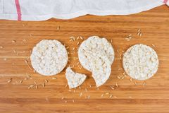 Puffed rice crispbreads among of whole grains on wooden surface. Top view of the dry round puffed crispbreads made from brown rice and other cereals among of royalty free stock image