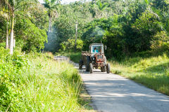 Puffs av rök följer den typisk gamla traktoren längs smalt lantligt r Royaltyfri Foto