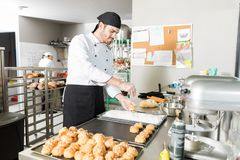 Puffs Of Choux Pastry Sprinkled With Pearl Sugar. Pastry chef sprinkling pearl sugar on choux in kitchen at bakery stock photo