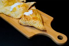 Puffs with cottage cheese. And sour cream on a wooden tray stock photo