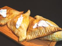 Puffs with cottage cheese. And sour cream on a wooden tray royalty free stock photos