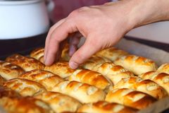 Puffs with curd on a baking tray. A man`s hand takes a puff with curd from a baking tray Stock Image
