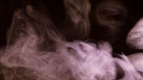 Puffs of smoke illuminated by colored light. Curls of colored smoke blurring against a dark background stock footage