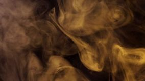 Puffs of smoke illuminated by colored light. Curls of colored smoke blurring against a dark background stock video footage