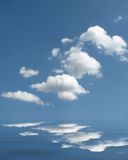 Puffy cloud reflections. Puffy clouds with reflections in ripples below Royalty Free Stock Photography