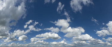Puffy clouds. Wide angle panorama of white puffy clouds on clear blue sky Royalty Free Stock Photo