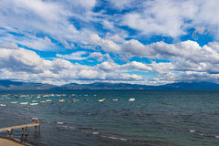 Puffy clouds above a Lake Tahoe pier Royalty Free Stock Images