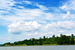 Puffy clouds. And blue  after he rain left from lake Livingston and the pretty shoreline with lots of trees of green Stock Photography
