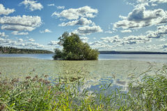 Puffy clouds, blue sky above a town on Malaren lake, Sweden stock photo