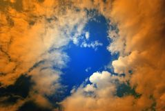 Puffy clouds with orange overlay Royalty Free Stock Photo
