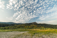 Puffy Clouds Over Green Landscape. Puffy clouds in a blue sky over green and rocky landscape in the Columbia River Gorge, Washington, USA Stock Photo