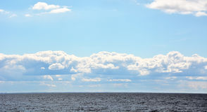 Puffy clouds over the sea Stock Photo