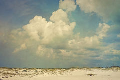 Puffy Clouds Over Sunny Dunes Landscape. Toned and artistically grunge textured, vintage style landscape of puffy cumulus clouds over sand dunes and sea oats Stock Images