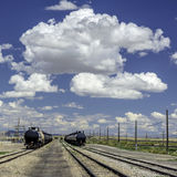 Puffy clouds over train cars Royalty Free Stock Photos