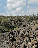 Puffy Clouds and Sharp Lava Rock Pile Stock Photos