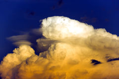 Puffy clouds at sunset above the Pacific ocean Stock Photos