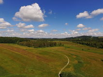 Puffy clouds under green land with forest Royalty Free Stock Image