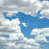 Puffy cumulus clouds on dazzling blue sky. Dazzling blue sky with white and puffy cumulus clouds. Sunlight illuminates the fluffy clouds and limitless blue sky stock photography