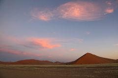 Puffy Pink Clouds over Red sand dunes Royalty Free Stock Image