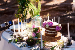 Puffy wedding cake with flowers. On decor table with candles Royalty Free Stock Photos