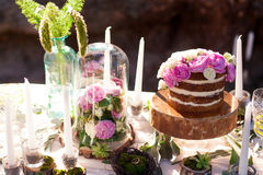 Puffy wedding cake with flowers. On decor table with candles Royalty Free Stock Image