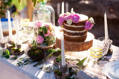 Puffy wedding cake with flowers. On decor table with candles Stock Photo