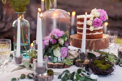 Puffy wedding cake with flowers. On decor table with candles Stock Images