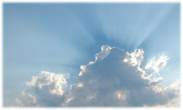 Puffy White Clouds against a Blue Sky. With rays of sunlight showing Royalty Free Stock Photography